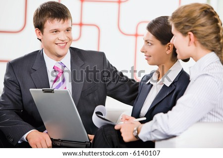 Business team of three people discussing a new project in room