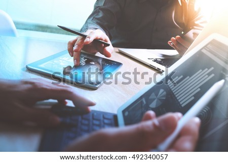 Business team present. Photo professional investor working new startup project. Finance meeting.Digital tablet laptop computer  smart phone using, keyboard docking screen foreground,filter