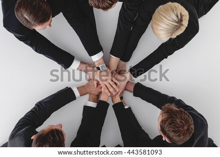 Business team stacking hands sitting around white table