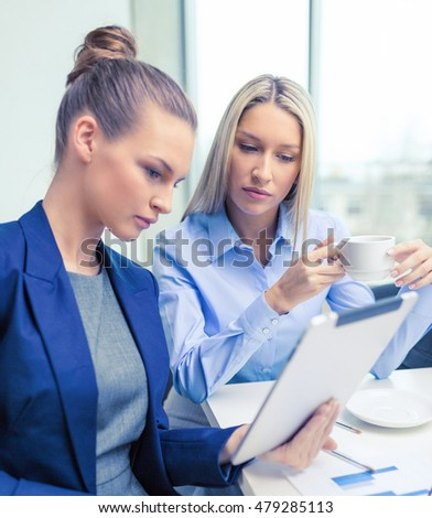 business, technology and office concept - serious businesswomen with tablet pc computers having discussion in office