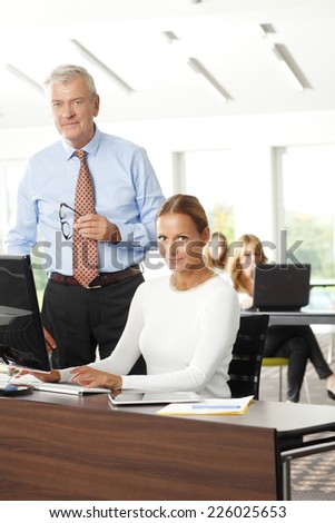 Business woman and businessman working together on laptop, while sitting at office.