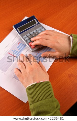 Business woman calculating over the stock chart