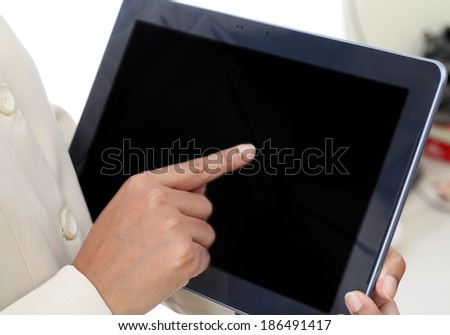 Business woman hand holding tablet with black display against white