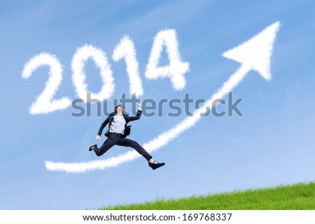 Business woman jumping over arrow sign with 2014 on the grass