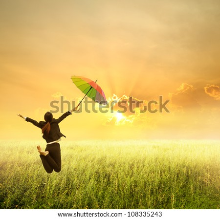 Business woman jumping to sunset in grassland with rainbow umbrella
