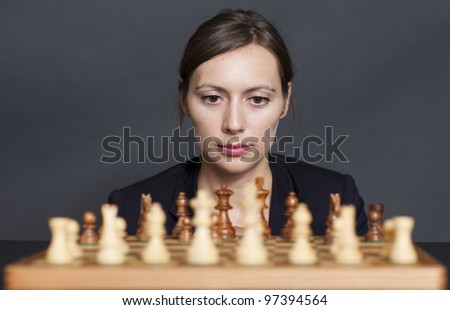 Business woman over a chess game
