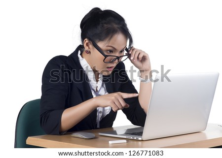 Business woman pointing at laptop's screen looking shocked and surprised, Isolated white background. Model is Asian woman.