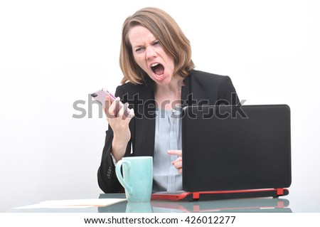 Business woman screaming into phone while at desk