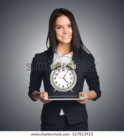 Business woman showing a metal alarm clock in front of him.