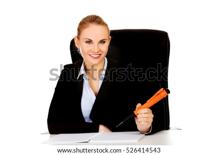 Business woman sitting behind the desk and writes something with big pen