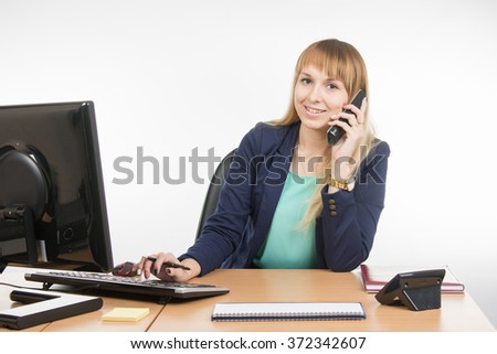 Business woman talking on the phone and working on the computer