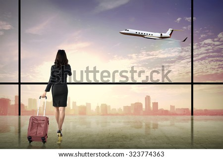 Business woman walking with suitcase over city background. Business travel concept