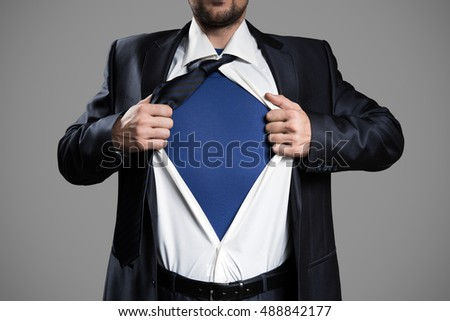 Businessman Acting Like A Super Hero And Tearing His Shirt, Isolated On Gray Background. Copy Space.