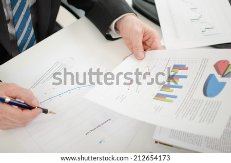 Businessman analyzing different graphs at his desk