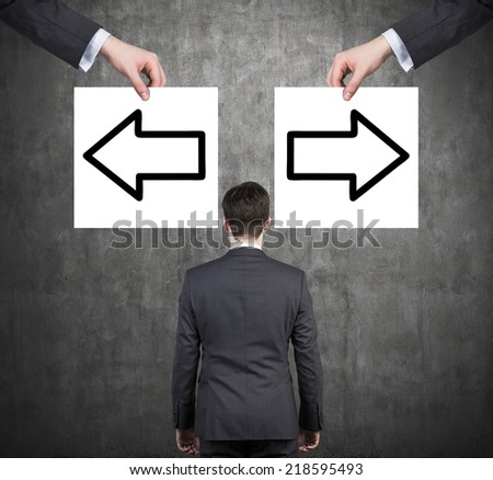 Businessman and arrows 'left or right'. Contradiction concept.