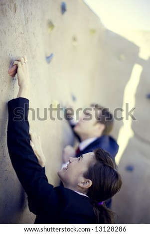 businessman and businesswoman climbing to the top of the wall