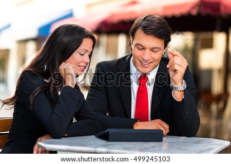 Businessman and Businesswoman Discussing Digital Tablet at Sidewalk Cafe