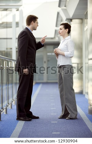 Businessman and businesswoman having argument in modern office building corridor