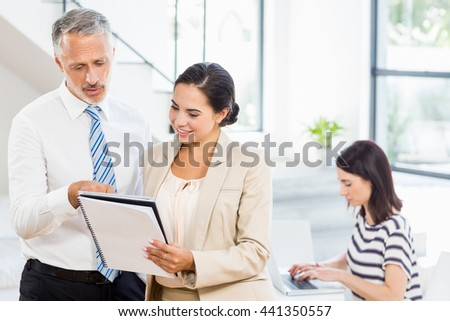 Businessman and businesswoman looking at diary while a colleague working on laptop in the background