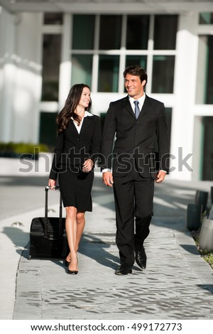 Businessman and Businesswoman Walking with Rolling Suitcase