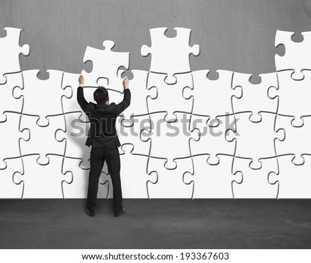 Businessman assembling puzzles wall