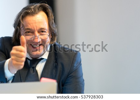 Businessman at desk showing thumbs up sign. Selective focus