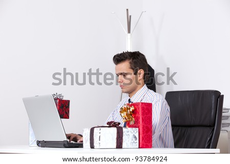 Businessman at his office working with his laptop with presents on the table