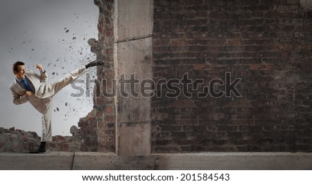 Businessman breaking stone wall with karate kick