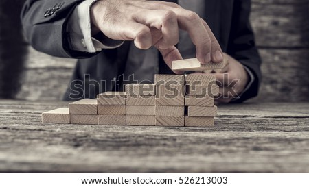 Businessman building a graph or ladder of success on old rustic wooden table.