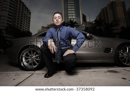 Businessman by a luxury car