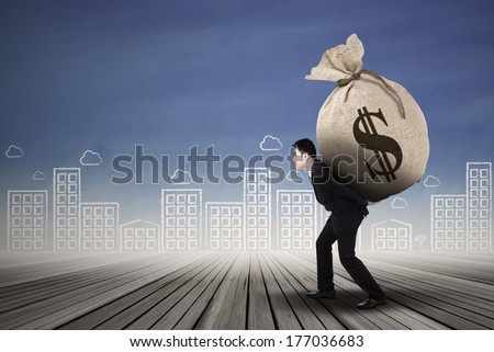Businessman carrying a money sack with US dollar sign outdoor