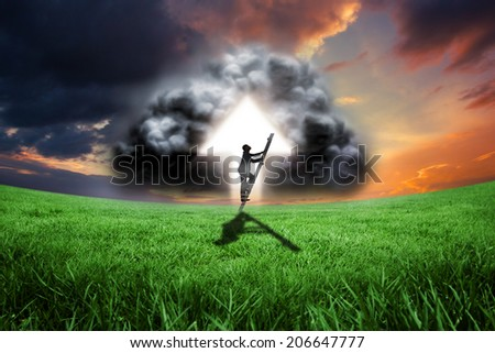 Businessman climbing up ladder against green field under orange sky