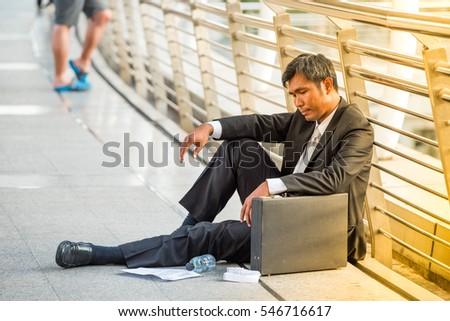 businessman fired from job sitting sad outside office in city background