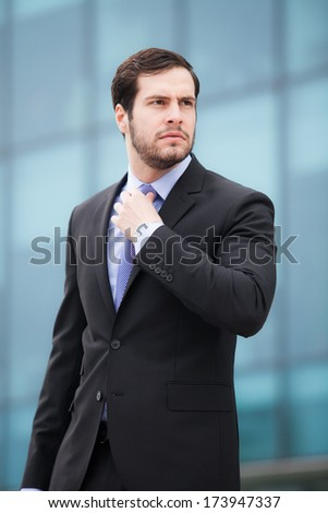 businessman fixing his tie looking serious in front of an office businessman