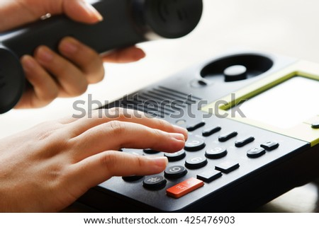 Businessman hand using telephone press number button