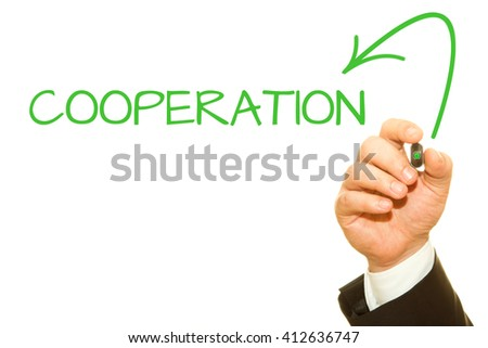 Businessman hand writing COOPERATION on a transparent wipe board.
