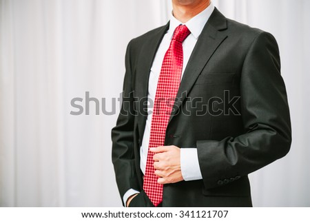 businessman has one hand in his pocket while holding his suit with another