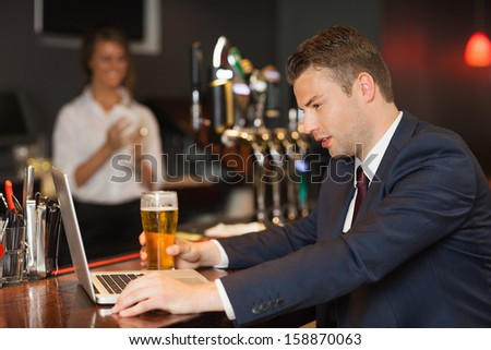 Businessman having a beer while working on his laptop in a classy bar