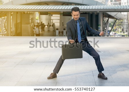 businessman holding a briefcase, powerful businessman