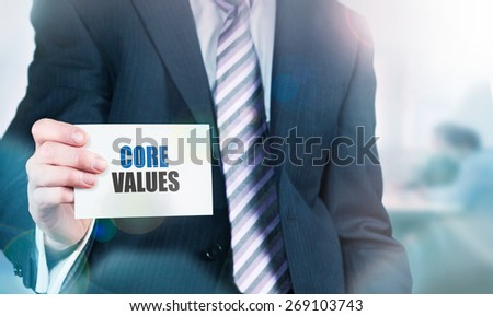 Businessman holding a card with Core Values written on it. Instagram styling applied.