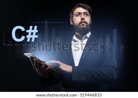 "Businessman holding a tablet pc with ""C#"" text on virtual screen."