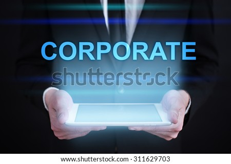 "Businessman holding a tablet pc with ""Corporate"" text on virtual screen. Internet concept. Business concept."