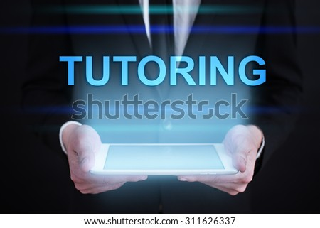 "Businessman holding a tablet pc with ""Tutoring"" text on virtual screen. Internet concept. Business concept."