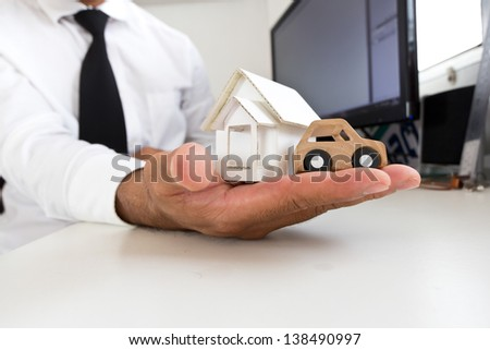 Businessman holding a wooden car and home on a table.