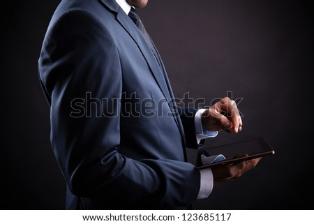 Businessman holding digital tablet on black background