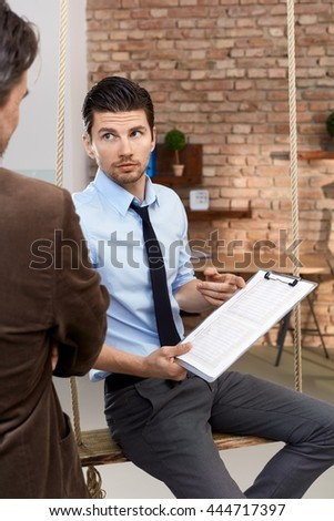 Businessman holding document, showing it to colleague, sitting in swing in modern office.