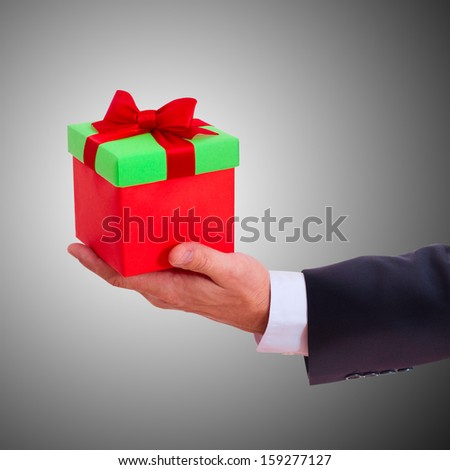 businessman holding gift box with red bow isolated