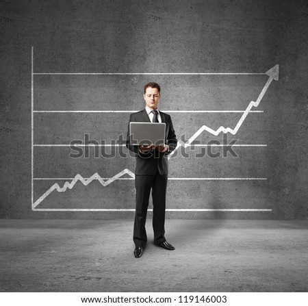 businessman holding laptop and profit on wall