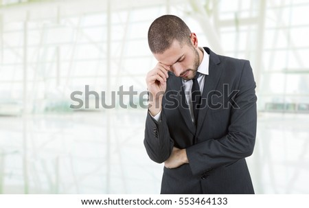 Businessman in a suit gestures with a headache at the office