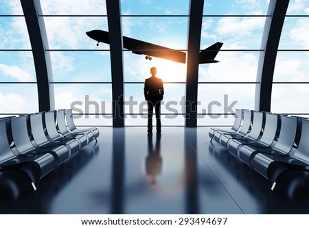 businessman in airport looking on airplane in sky